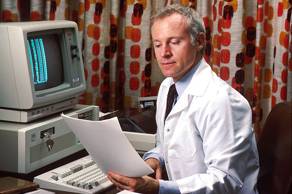 Doctor sitting by 1980s computer reading a report